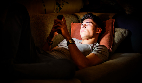 Teen age male up late on phone.