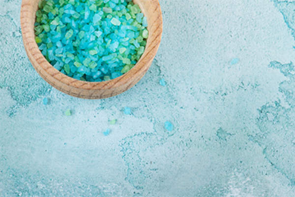 Bowl of mineral bath salts in bathroom.