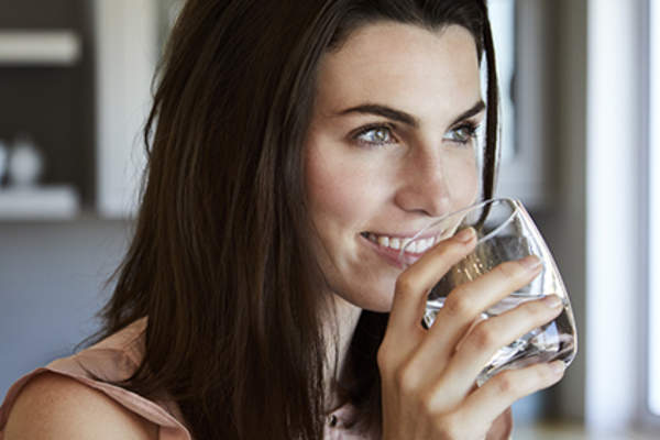 Smiling young woman drinking a glass of water.