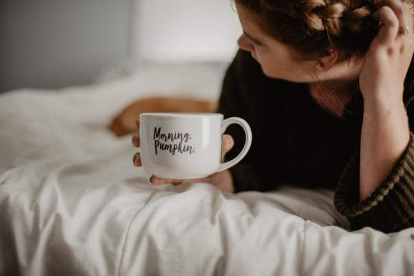 "woman in bed holding mug that reads ""morning, pumpkin."""