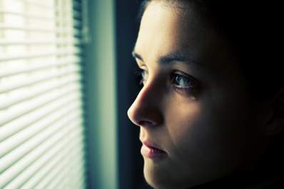 young woman crying looking out window image