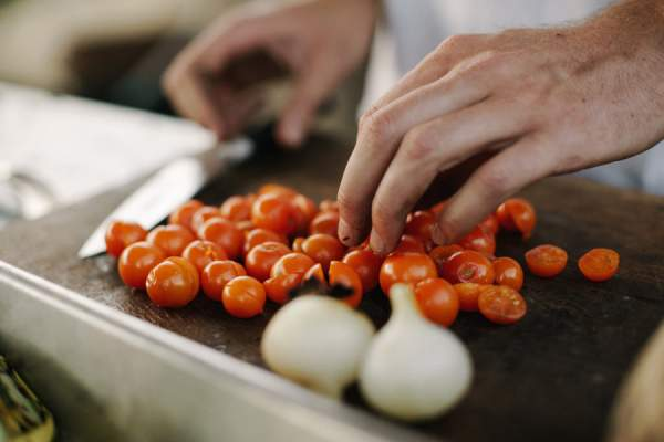 man's hands cutting up tomatoes