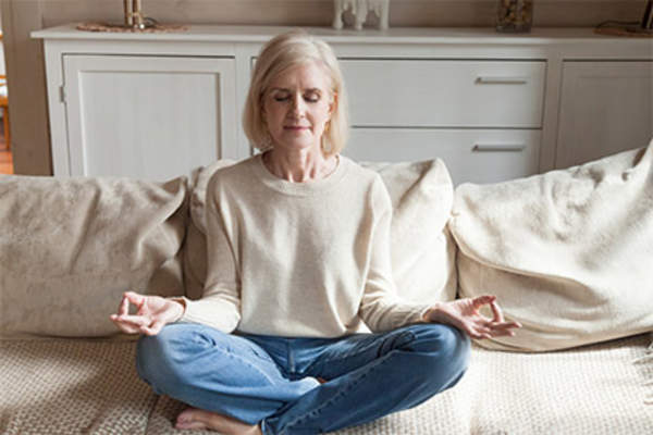 Woman meditating at home on couch.
