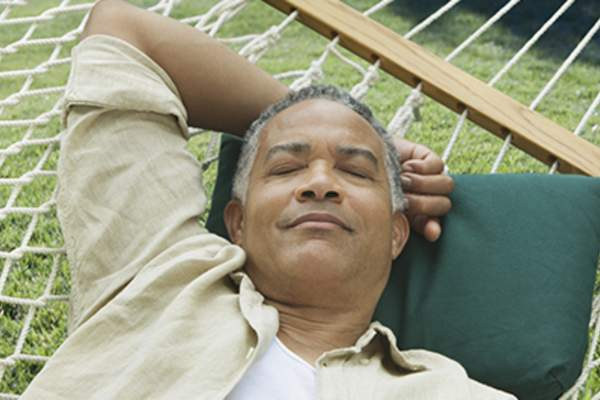 Older man sleeping on a hammock.