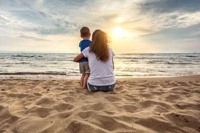 Mother and young son watching sunset on the beach.