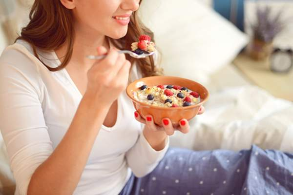 A woman eats a breakfast featuring strawberries and blueberries.