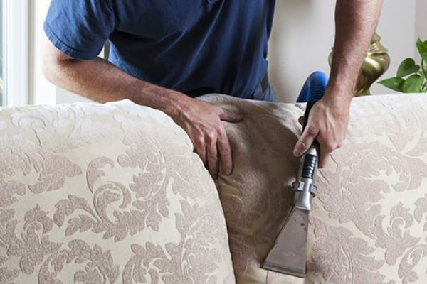 man vacuuming couch image