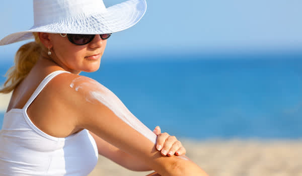 Woman putting on sunscreen at beach.