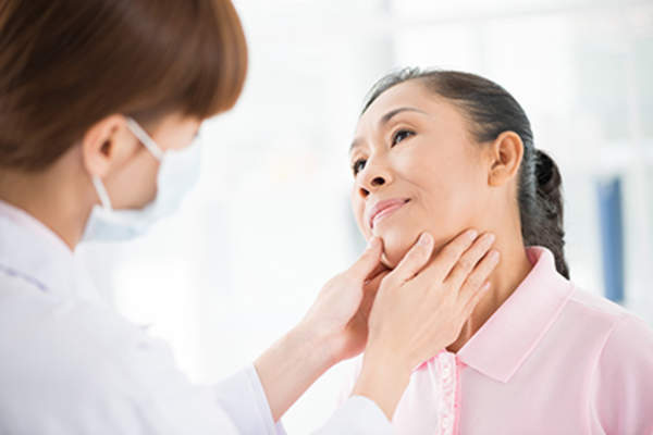 Adult woman undergoing thyroid examination.