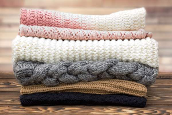 Winter knitted clothes stack on wooden background