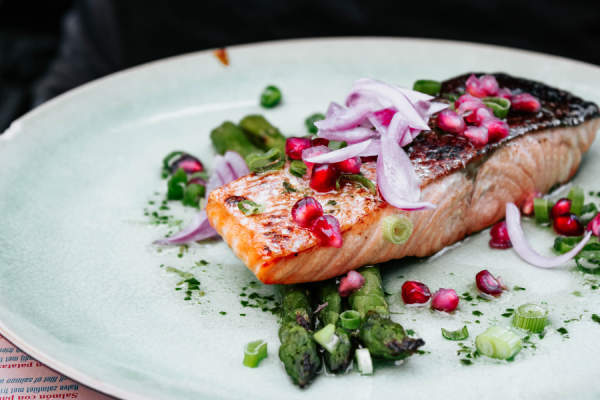 salmon on plate with pomegranate seeds and asparagus