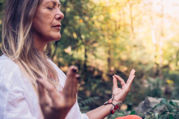 Mature Woman Meditating in Forest