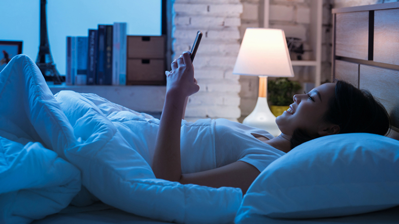 Woman using her phone in bed.