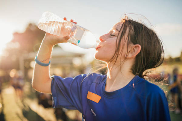 girl drinking from water bottle during soccer practice
