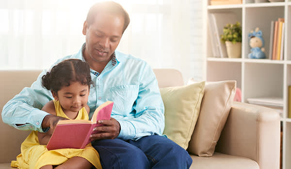 Father reading to young daughter.