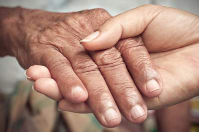 Caregiver concept old hand in young hand.