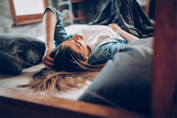 Uncomfortable young woman lying on her bed.