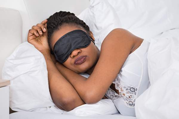 Sleeping woman wearing eye mask.