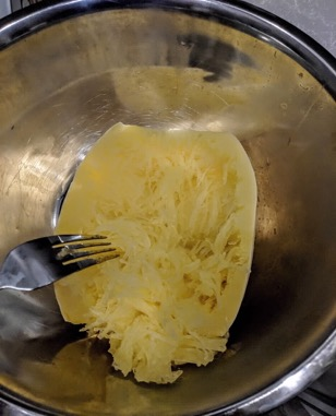 Shredding a spaghetti squash with a fork.