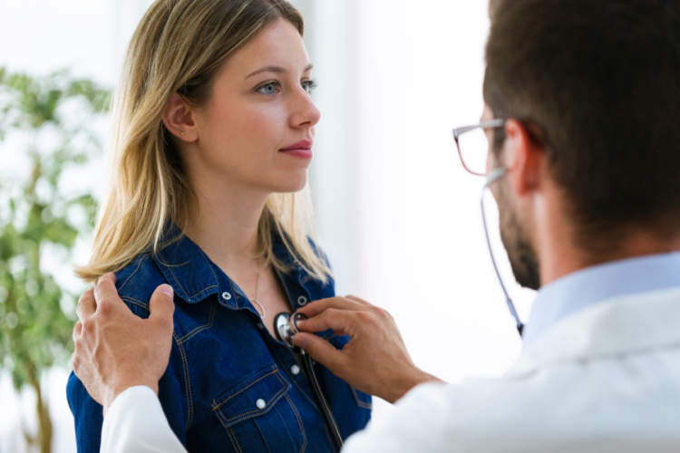 young woman getting heart checked with stethoscope