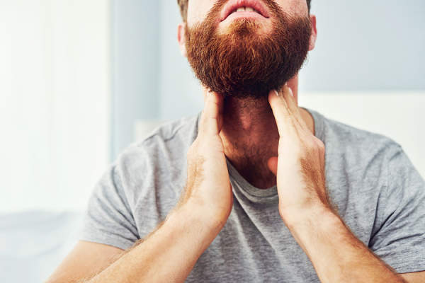 Man checking his neck for swollen lymph nodes