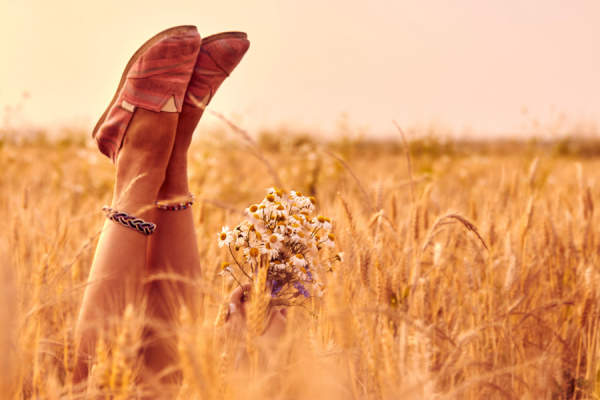Girl holding flowers and lying in a wheat field, wearing comfortable shoes