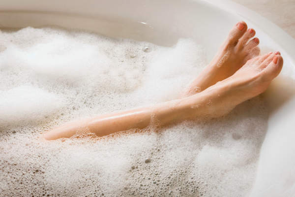 Woman's legs while she's relaxing in a bubble bath.