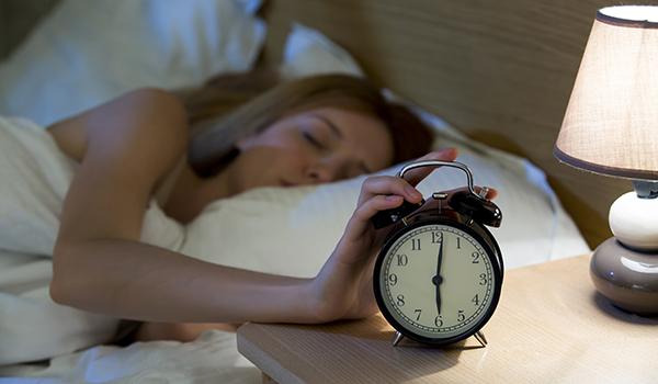 Woman sleeping in bed and touching alarm clock.