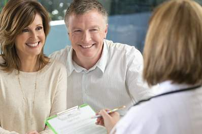 Doctor filling out form with mature couple.