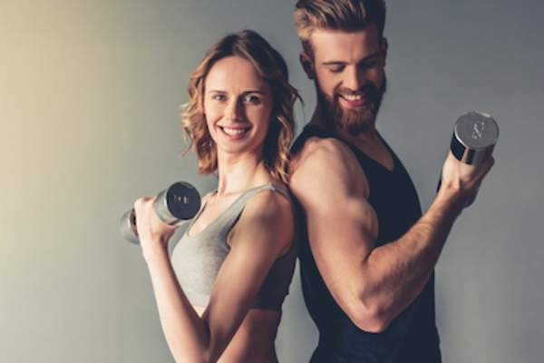 Sporty man and woman back to back curling dumbbells.