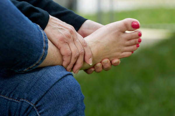 Woman holding foot, foot pain concept.