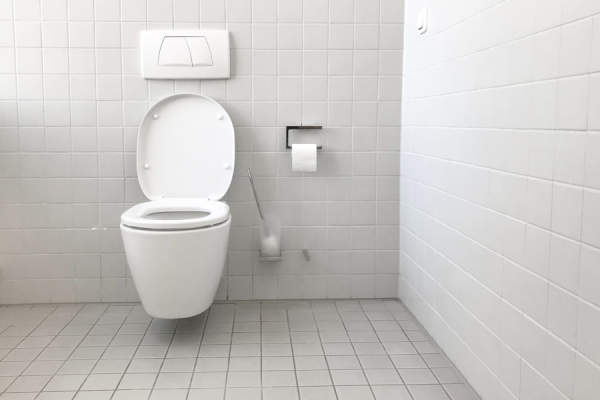 toilet in white tiled room