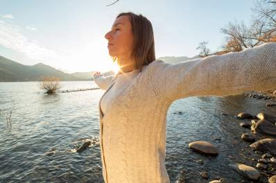 Empowered woman with outstretched arms by a lake.