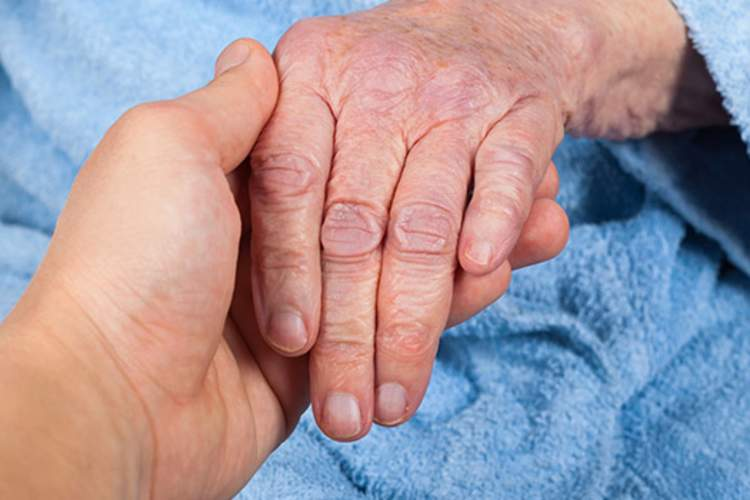 Holding senior's left hand.