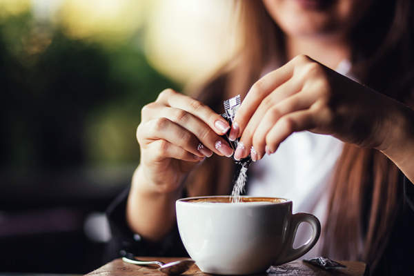Woman pouring packet of artificial sweetener into coffee
