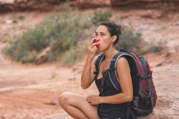 Female hiker stopping to use inhaler.