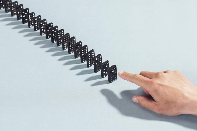 hand about to knock down line of dominoes