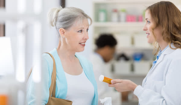 Pharmacist reminding patient of drug interactions.