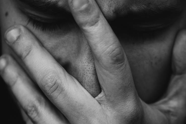 black and white photo of anxious man with hand on face