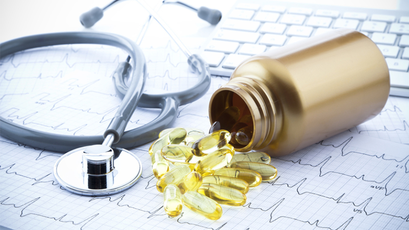Fish oil supplements and heart health concept with stethoscope.