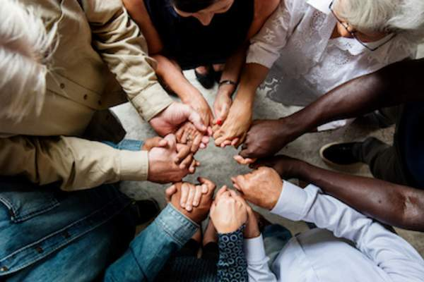 Support, diverse group hands in circle.
