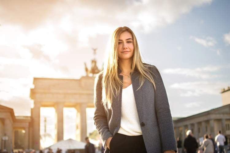 Smiling fashionable young woman in front of Brandenburger Tor in Berlin, Germany.