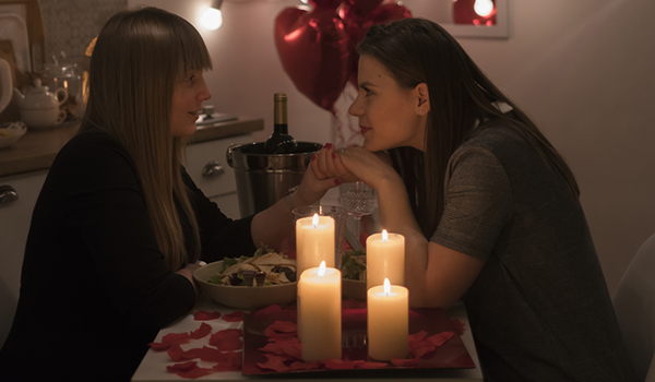 Women having a romantic dinner at home for Valentine's Day.