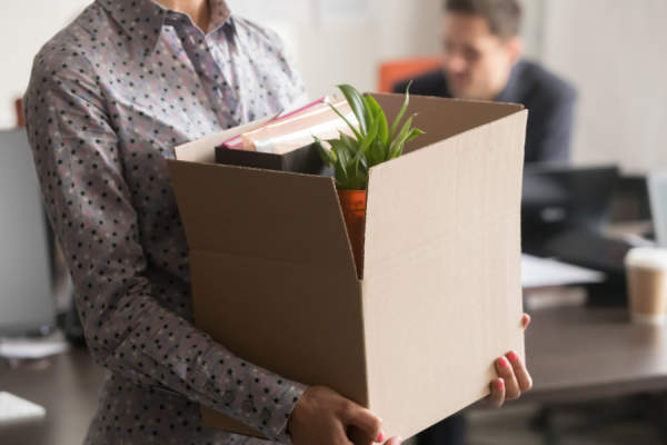 employee carrying cardboard box of her stuff out of an office