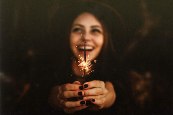 Happy woman holding sparkler