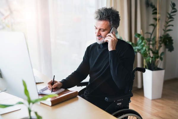 Mature man in wheelchair with smartphone in home office.
