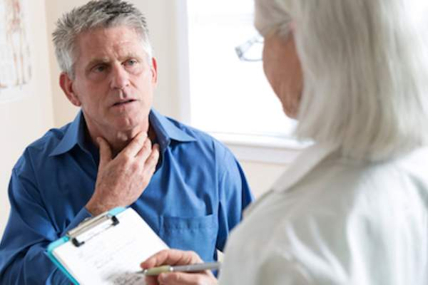 Man explaining symptoms to doctor.