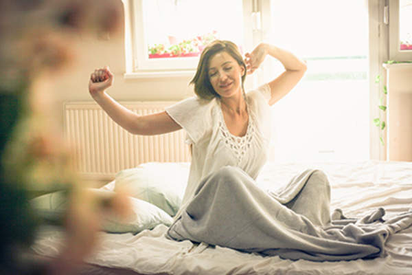 Woman waking up with a smile.