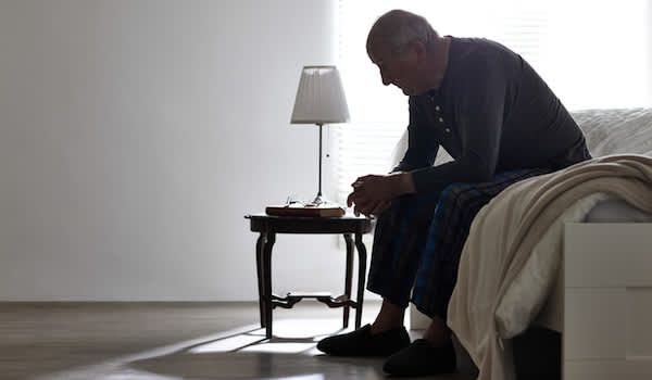 Older person depressed staring at floor.