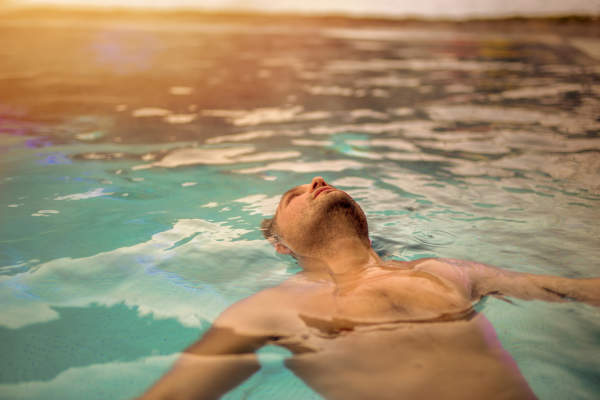 Man floating on back relaxing in pool.